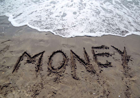 great text MONEY that is canceled by the sea wave on the sandy beach