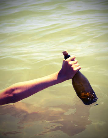 hand who take a bottle with secret message in the ocean with vintage effect Stock Photo