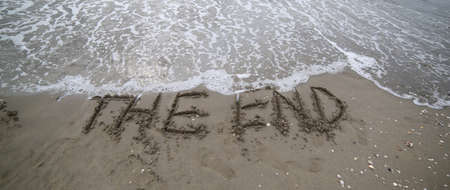 wide text THE END that is deleted by the sea wave on the sandy beach Stock Photo