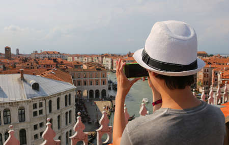 young photographer with hat and with smart phone takes pictures of old palaces and grand canal in Venice Italy Stock Photo