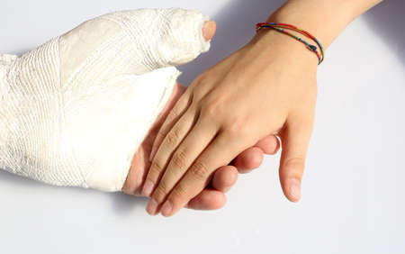 man with a fractured hand and a plaster cast at the hospital and the hand of his little girl