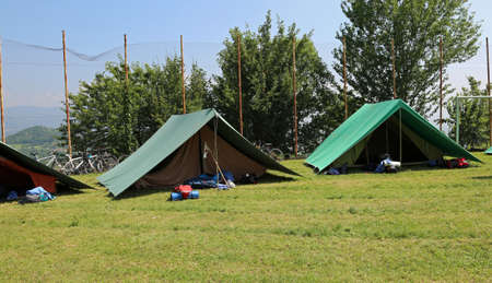 two green tents mounted by scouts in a meadow to spend the night