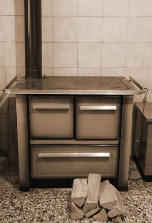 old wood-burning stove inside the kitchen of the home in mountain with sepia effect Stock Photo