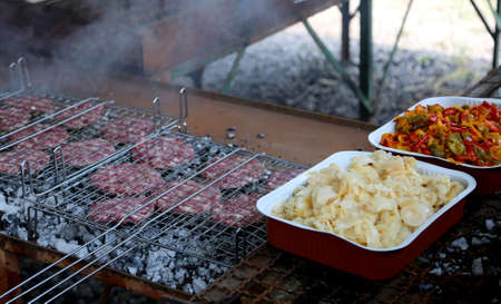 barbecue with burgers to cook on an outdoor fire Stock Photo