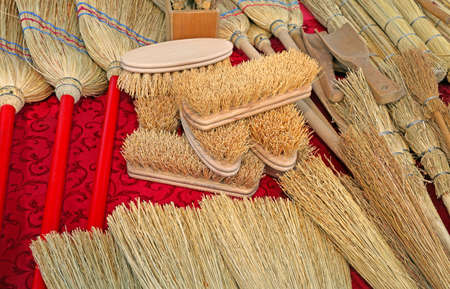 many brushes and small brooms in sorghum for sale at market