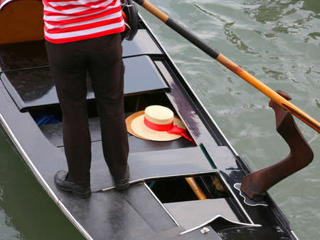 Typical gondolier on the gondola and his boater in Venice Italy