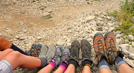ten hiking boots of a family of five persons in mountain Stock Photo