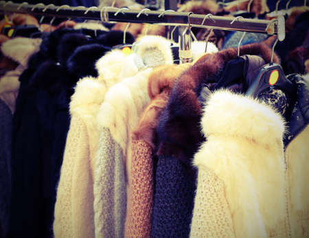 many vintage clothes and fur for sale at flea market with vintage effect