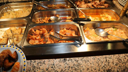 many trays with fried food in a self service Chinese restaurant Stock Photo