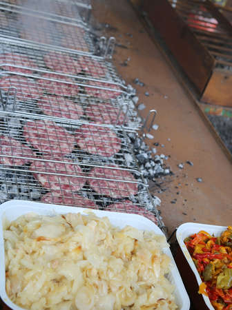 tray of onions and peppers at the restaurant with lots of burgers cooked on the grill