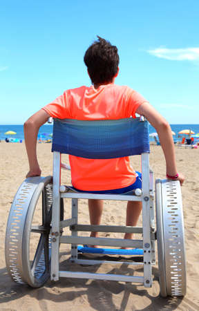 Special wheelchair with wide wheels to go on the sand of the beach