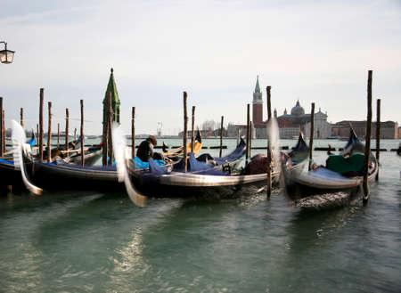 three moved Gondolas in Venice in Italy with long exposure effect