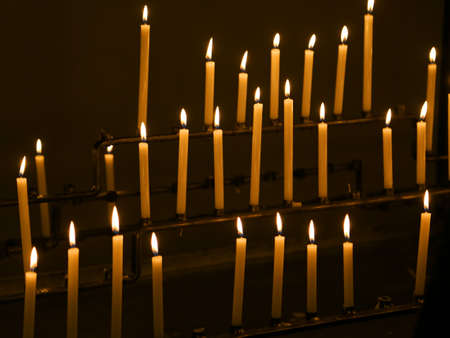 many candles with flames in the place of worship
