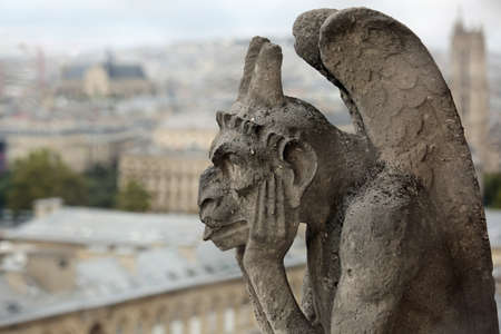 thinking figure called Chimera or grotesque in Paris France from Bell tower of Basilica of Notre Dame