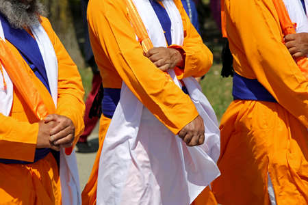Sikh soldiers with orange and white traditional dress participate in a religious event