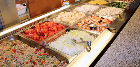 trays full of pasta dishes and side dishes of vegetables with tomato, fish salad and other goodness