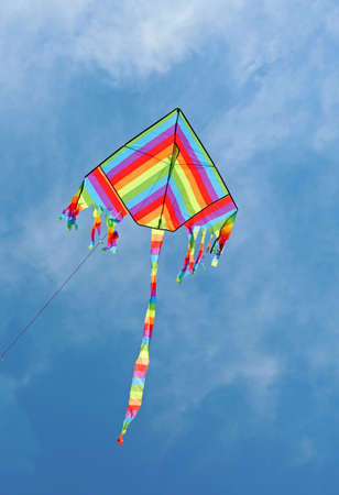 kite with the colors of the rainbow flies high in the blue sky Stock Photo