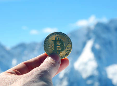 bitcoin money on the hand of a man and mountains on background