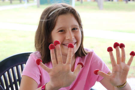 smiling beautiful little girl with red raspberries on fingers hands Фото со стока