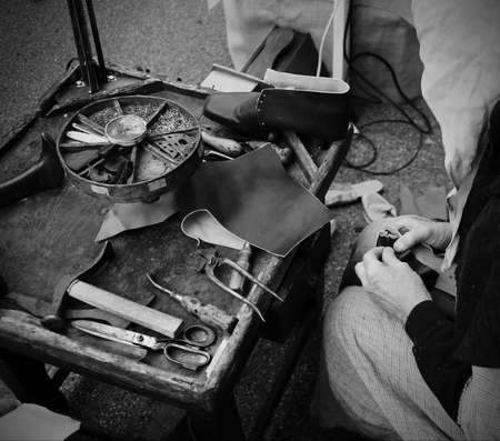 ancient workshop with expert shoemaker during the processing of leather to