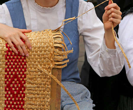 girl with tapering fingers of the hand creates patiently a straw bag