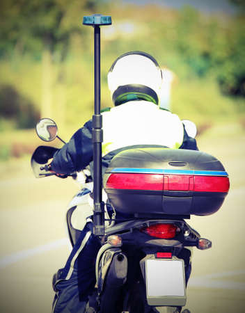 policeman with helmet on the police motorcycle while patrolling the street with vintage effect Stock Photo