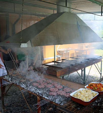 many grills with hamburgers and tray with peppers and onions at a festival