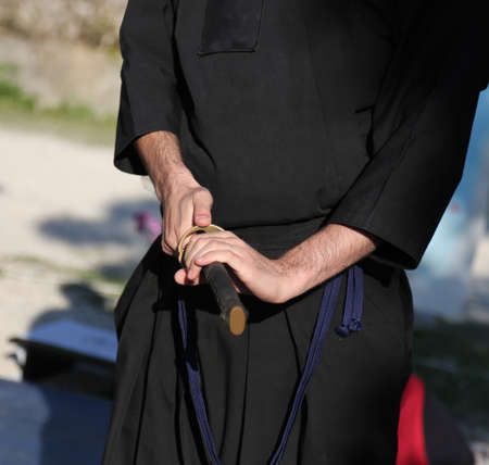 warrior specialized in martial arts with a sword in his hand during physical exercises and black dress Stock fotó