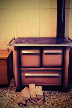 ancient wood stove in the kitchen of the small house with vintage effect Stock Photo