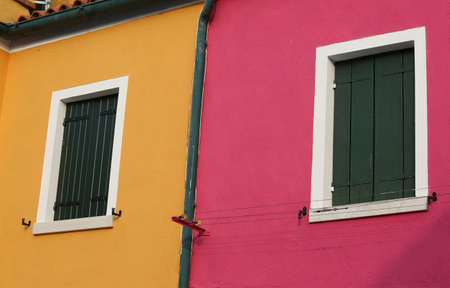 green balconies of two colored houses in the island of Burano near Venice