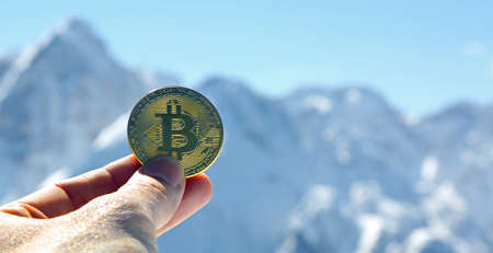 golden coin of bitcoin money on the hand of a man and mountains on background