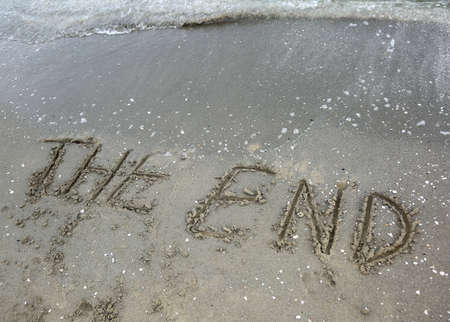 word end written on the sand of the beach