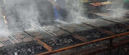 smoke rises from the grids on which beef burgers are cooked for the village fair Stock Photo