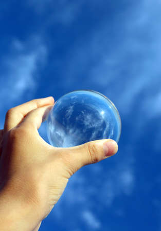 hand with a transparent sphere facing the sky