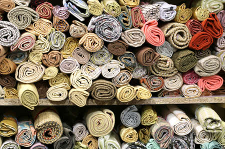 rolls of fabric of different shapes and colors displayed at a fair