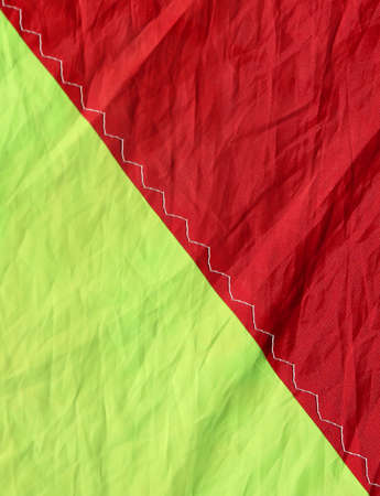 Nylon fabric in two bright red and yellow colors divided in half with a seam Stock Photo