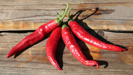 four spicy red peppers on a brown wooden table
