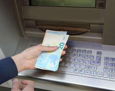 Young boy at ATM and many Euro banknotes in Europe