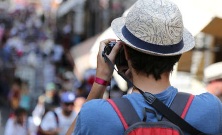 boy with a hat photographs people walking down the street