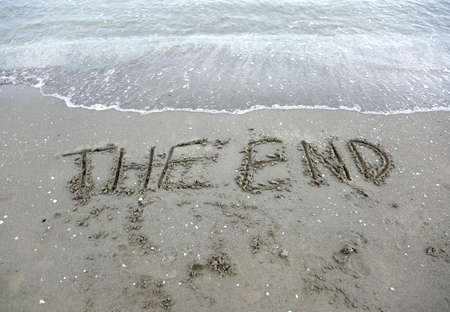 very big text THE END on the ocean shoreline without people and a wave