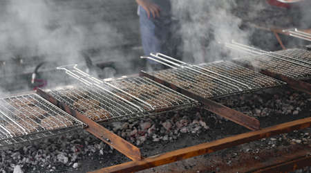smoke rises from the grills with hamburgers cooked for a barbecue
