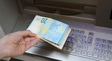boy takes banknotes euro with hand at ATM in Europe
