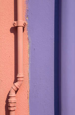 wall of a typical Burano Island house divided in half and painted in orange and purple