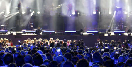 many heads of the audience of the live concert while recording and photographing the musicians with modern smartphones Stock Photo