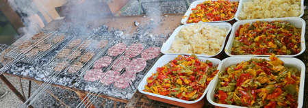 trays of peppers and onions near grills with many burgers cooked for a festival
