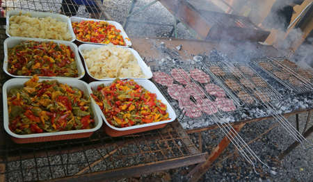 trays with onions and peppers next to the grills with the burgers at a barbecue 免版税图像
