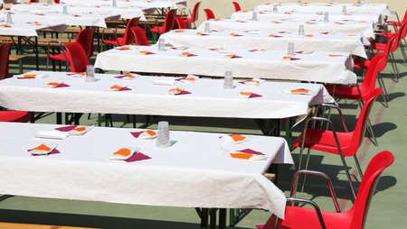 many tables set outdoors for a community lunch Banco de Imagens