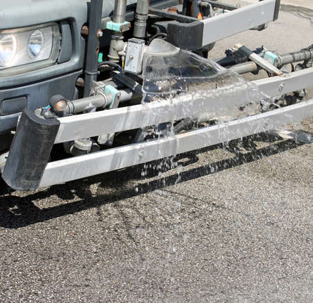 modern truck for washing the road with water spray on the asphalt