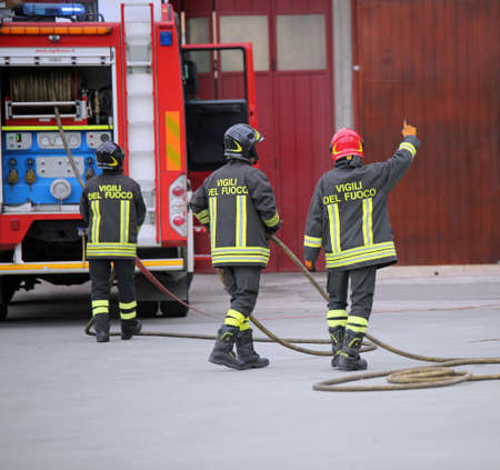 Italia, Italy - May 10, 2018: three Italian firefighters and the fire truck  with uniform and text Vigili del fuoco that means Firemen in Italian language during a practical exercise. The fireman with red helmet is the leader