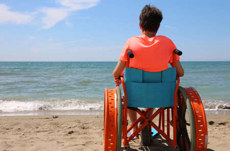boy on the special wheelchair with metal wheels on the beach by the sea Stockfoto